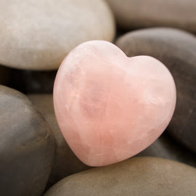 Rose quartz heart on pebbles